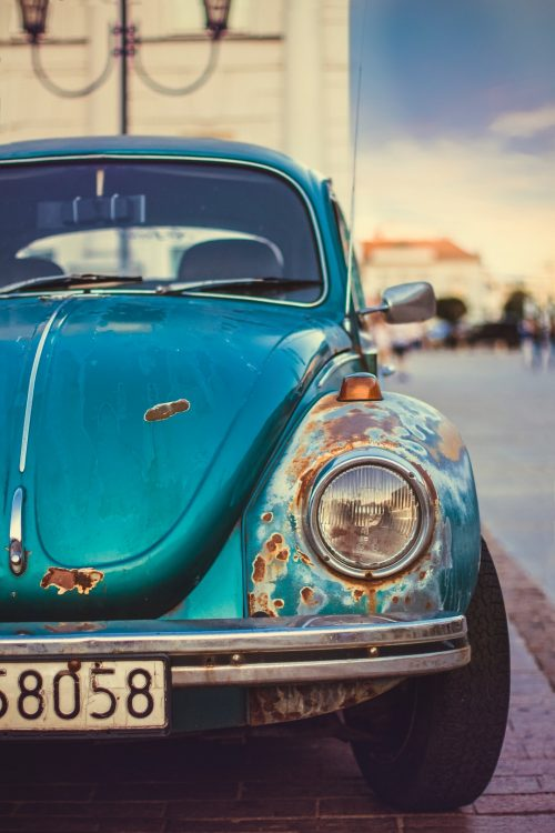 an old blue rusty car on the road